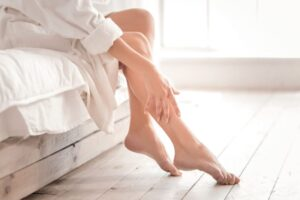 A woman feeling her leg for hair.