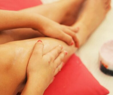 A woman rubbing essential oils on her leg to get rid of cellulite.