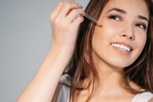 Applying pore minimizing serum on face.