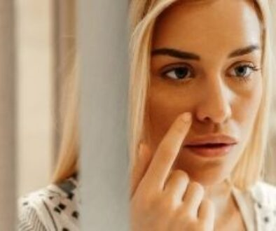 Woman staring her face in front of the mirror